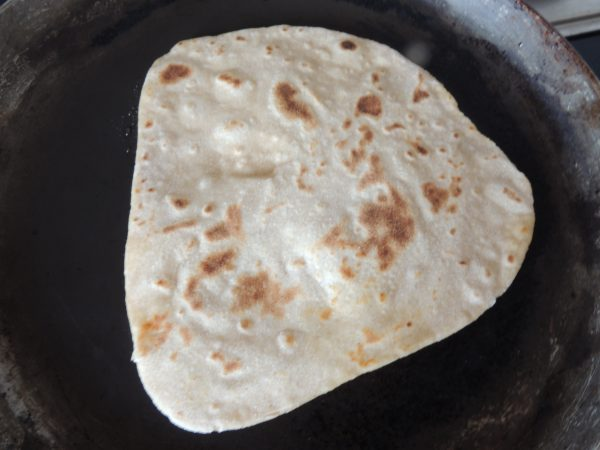 Now flip the paratha again with spatula.