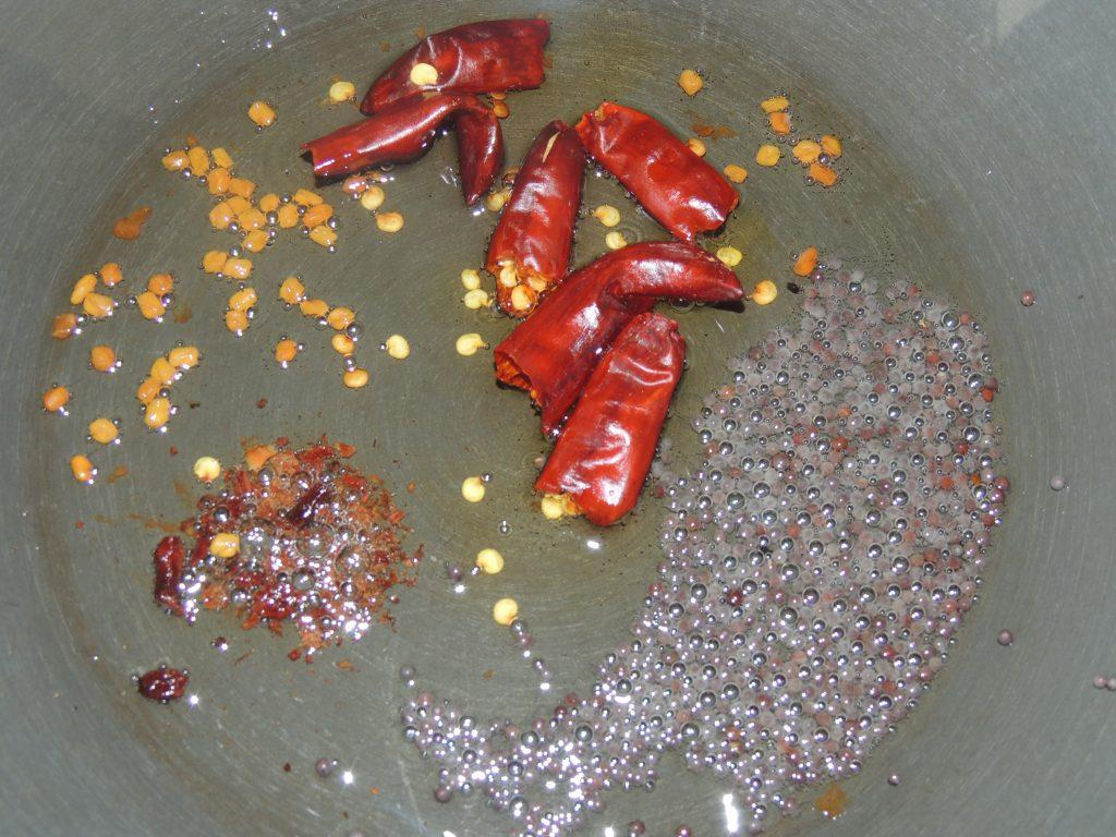 Oce the oil become hot, add fenugreek seed, mustard seed, and broken coriander seed, broken cloves into kadai.