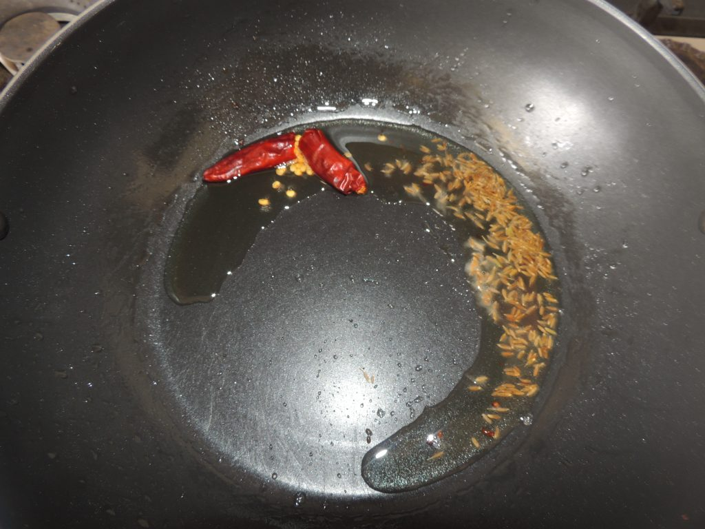 When the oil is hot, add cumin seeds and red chili.