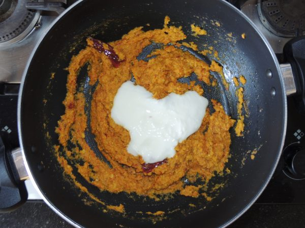 Now add two spoonfuls of beaten curd to the spices.
