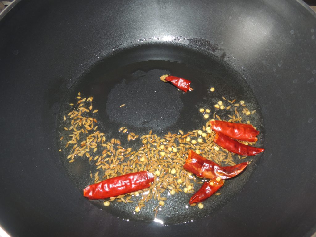 Then add cumin seeds to the oil. When the cumin seeds start crackling add red chillies.