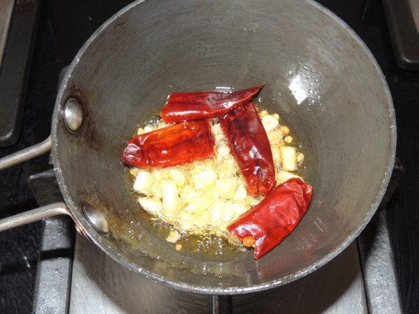 Stir garlic with spoon. Let fry garlic for 30 seconds. After that add pieces of red chilli.