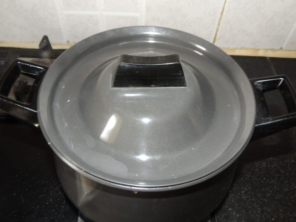 Once the water starts boiling. Place the lid on the handi / fry pan.