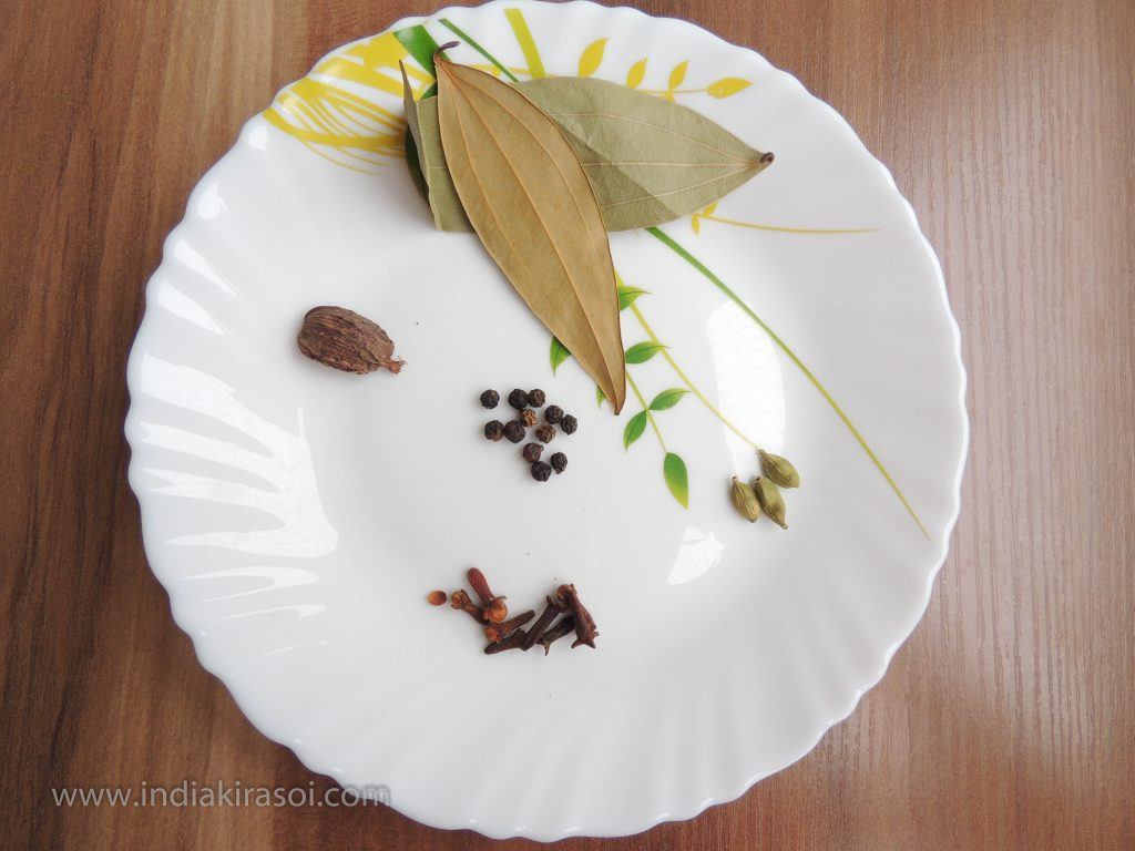 Now take big cardamom, black pepper, bay leaves, cloves, green cardamom.