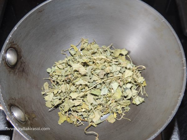 When the fry pan is hot, add one spoon of Kasuri methi to the pan and stir it with a spoon.