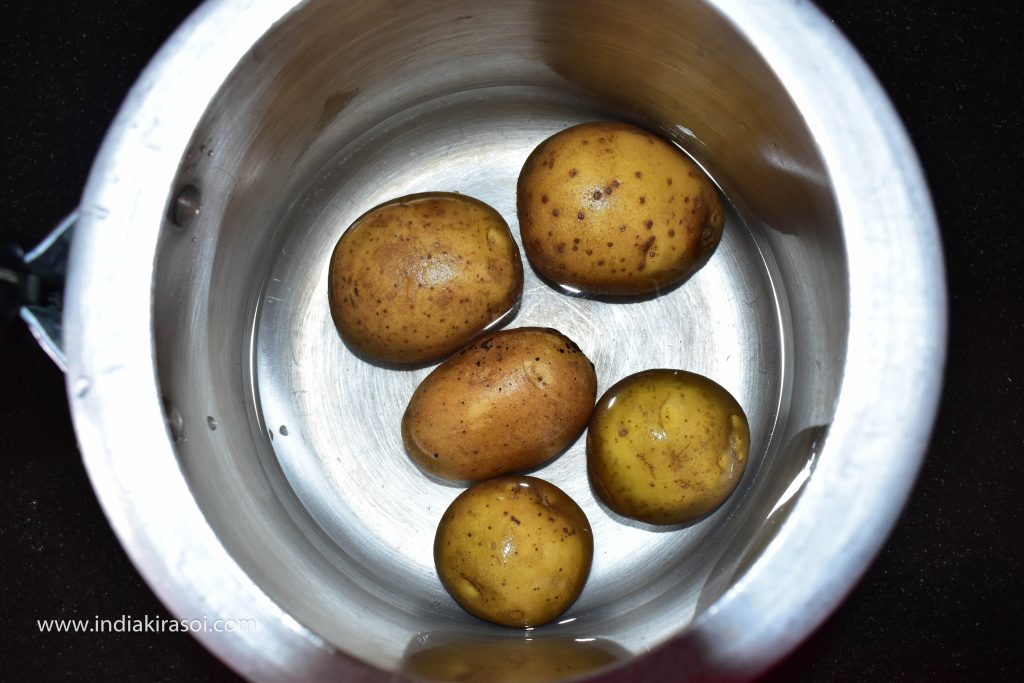 To make stuffed capsicum, first boil 3-4 potatoes in a pressure cooker.