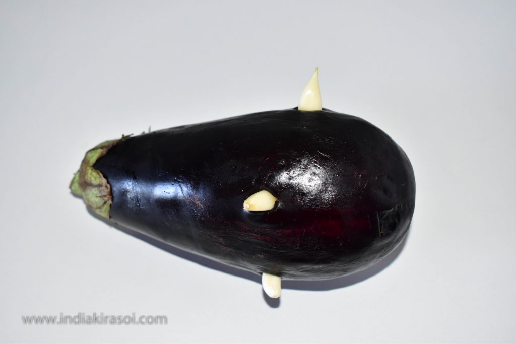 Peel 4 garlic. And put the garlic eggplant in a small hole so that half the garlic remains inside the eggplant and half outside the eggplant.