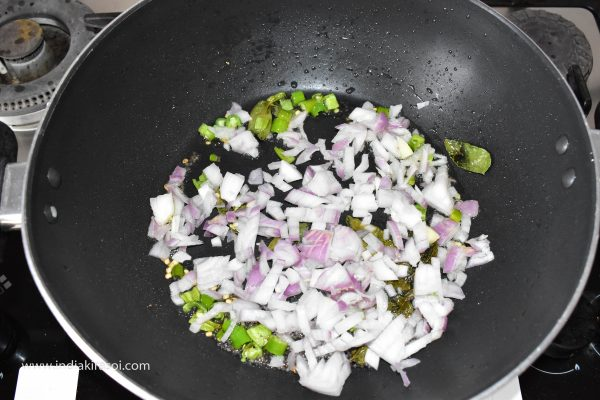 When the green chillies fry lightly, add chopped onions to the kadai / pan.
