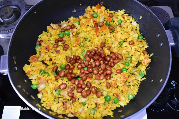 Then add fried peanuts and half a teaspoon red chili powder to the poha and fry for one to two minutes.
