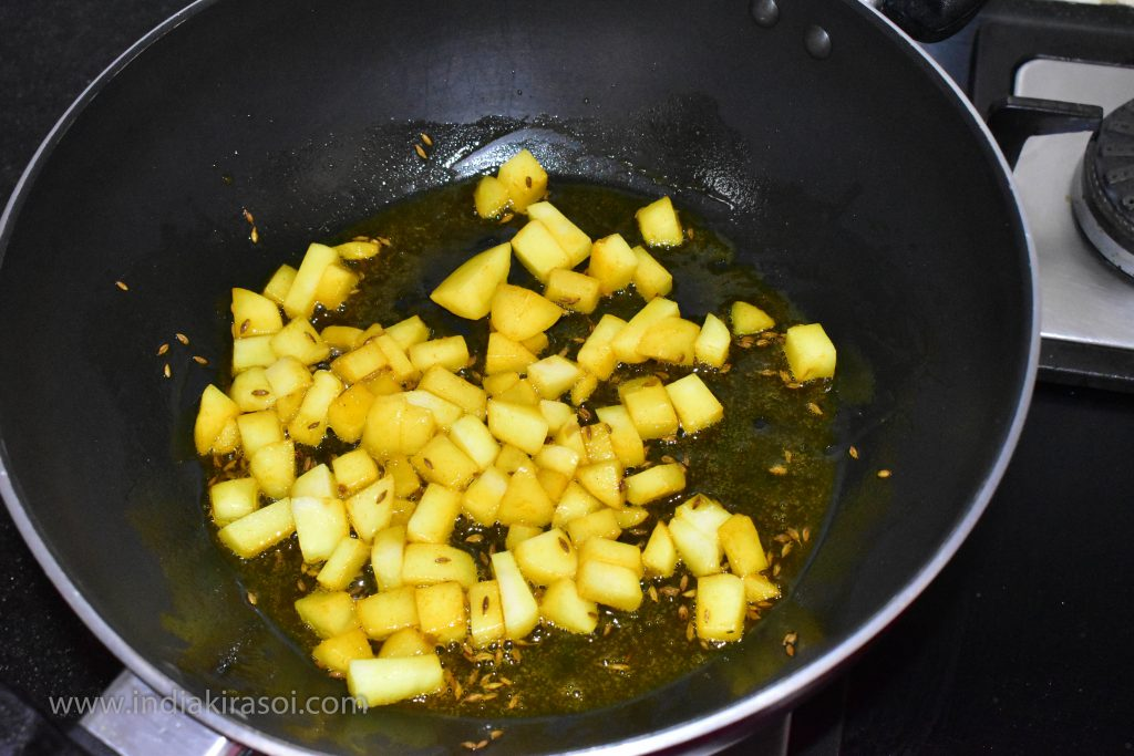 Now add chopped potatoes in the kadai / pan. Pour some salt over the potato.
