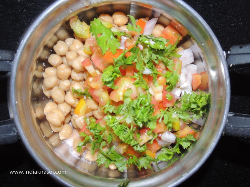 After this, take the cooked chickpeas, chopped onions, chopped tomatoes and chopped green chilies in a vessel.
