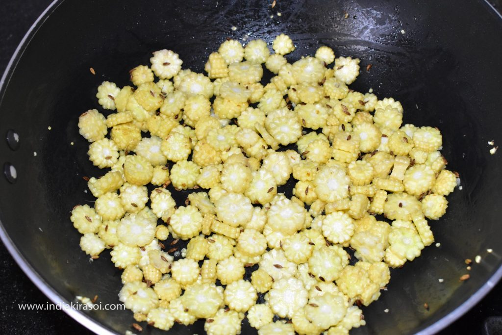 When the cumin seeds crackle, add chopped baby corn.