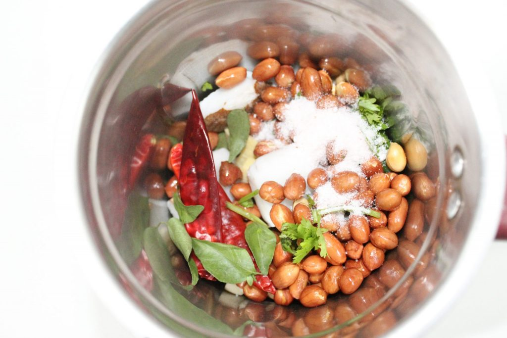 With coriander leaves, 2 green chilies,1.5 tsp roasted gram, 1 inch chopped ginger, 6 to 7 curry leaves, 2 whole red chilies, 4 chopped garlic.