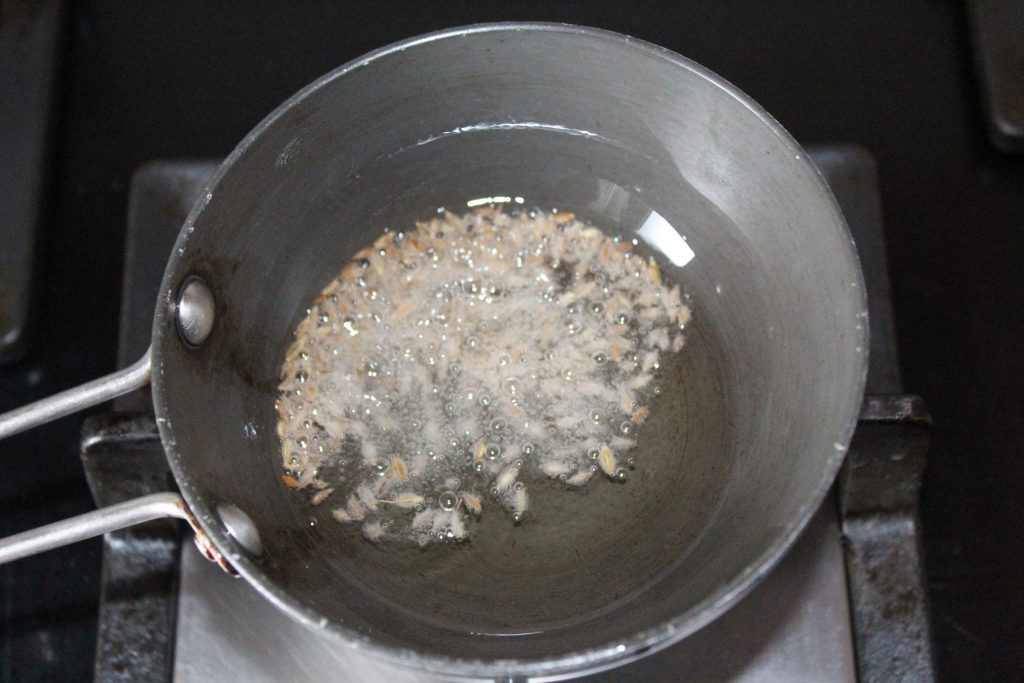 When the oil is hot, add one spoon cumin seeds to the oil.
