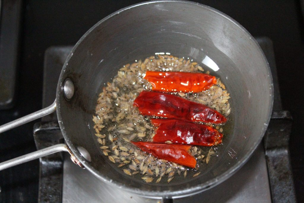 When the cumin starts crackling, add 2 whole red chilies (cut in two pieces) in it.