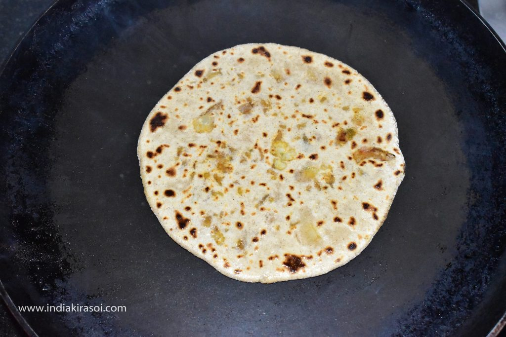 Take one teaspoon of oil or desi ghee in a spoon and spread it on the paratha. Apply oil or desi ghee on the whole surface of the paratha.