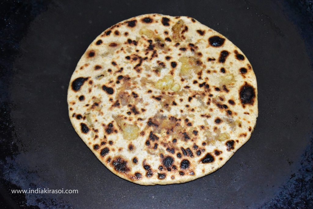 Now again change the side of the paratha, and apply oil or desi ghee on the other side as well.