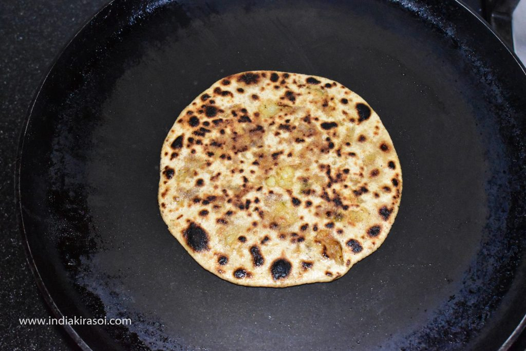 Press and roast the paratha with the help of a spoon.