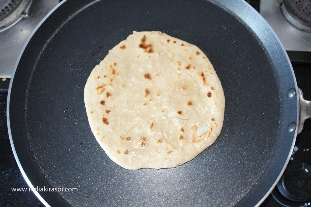 And on the other side of the paratha also apply a spoon of oil or desi ghee.