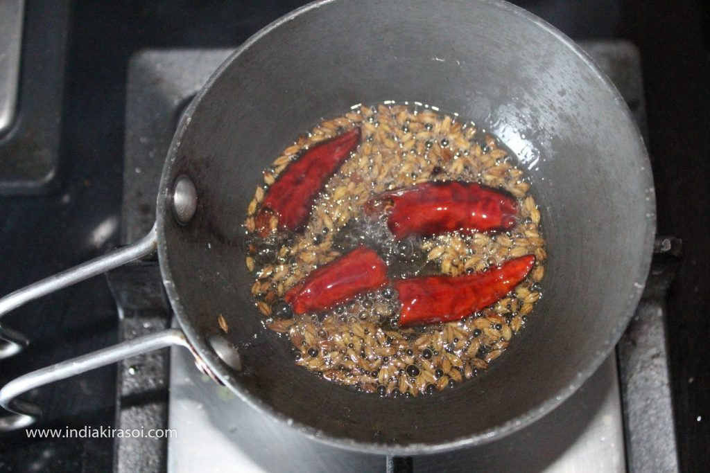 When the cumin/ jeera starts crackling, break two red chilies and add them to the ghee.