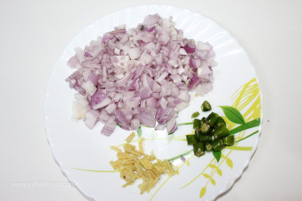 With this, take 2 medium size onions. Finely chop the onion. Take 1.5 inch piece of ginger. And peel the skin, and cut the ginger into long slices. Keep in mind that ginger is finely chopped. Also, take a green chili and chop it,