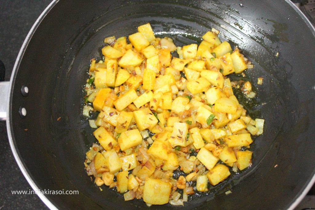 Now mix potato, onion, turmeric, and salt with a spoon.