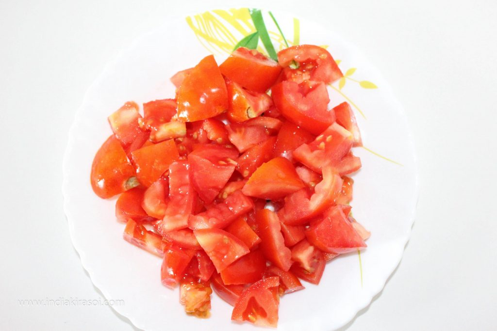 Take 2 medium-sized tomatoes, chop the tomatoes and put them in the jar of the mixer grinder.