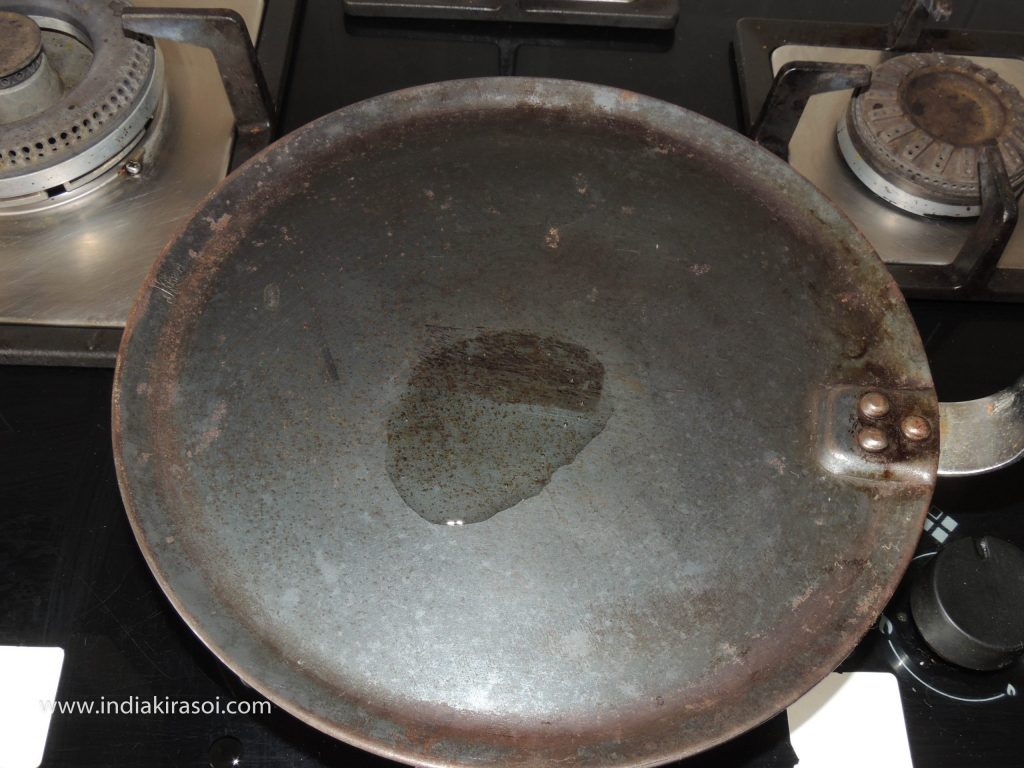 When the griddle/ tawa gets hot, add one teaspoon of oil to the griddle/ tawa.