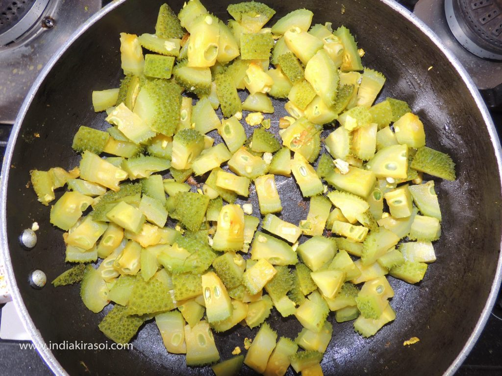 Open the plate of kadhai/ fry pan after 3 minutes and check if the spiny gourd/ kateele parwal/ kantola is cooked.