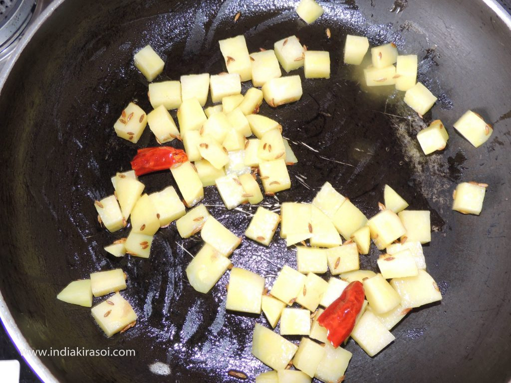 When the cumin seeds start crackling, put the chopped potatoes in the pan.