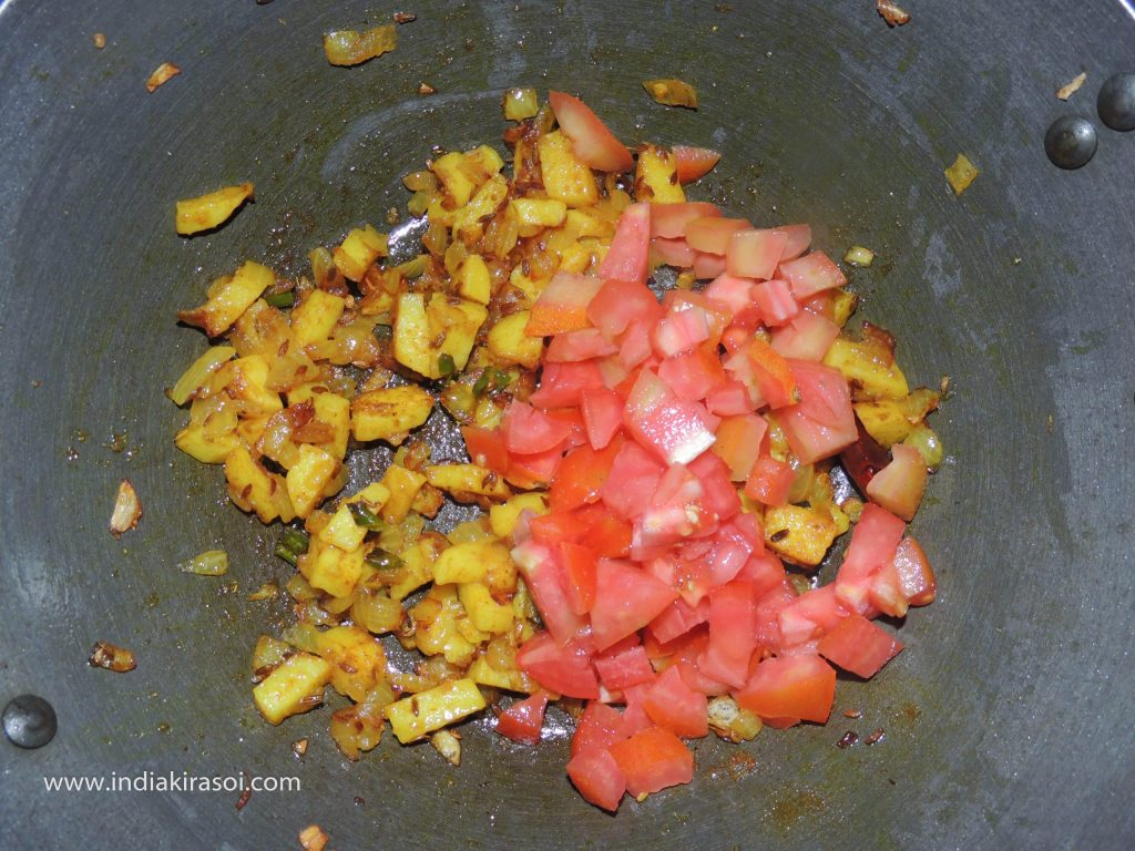 When the potatoes are cooked, add chopped tomatoes in the kadhai/fry.