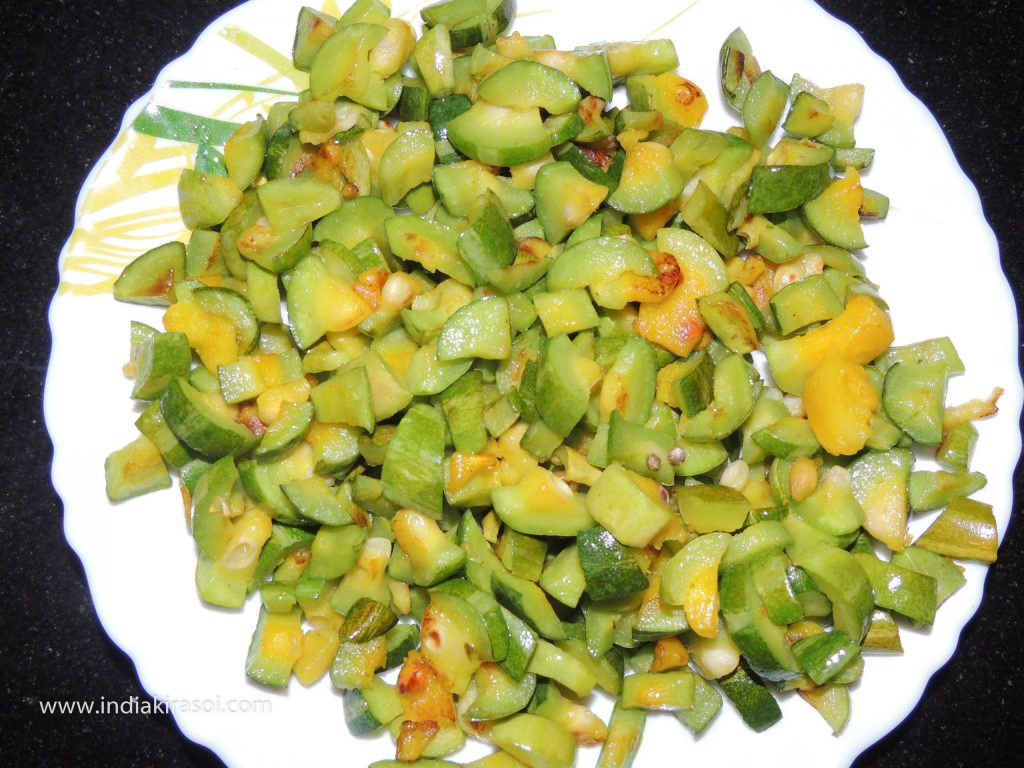 After frying the pointed gourd/ parwal, keep the pointed gourd/ parwal aside in a plate.
