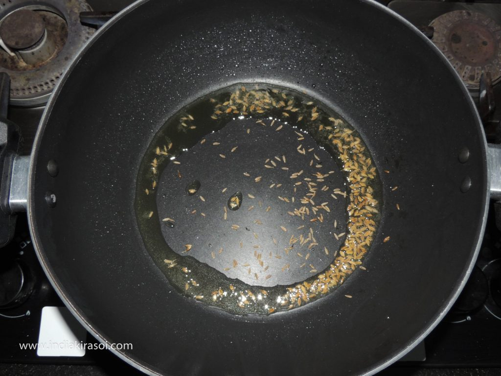 When the oil is hot, add half a teaspoon of cumin seeds to the oil.