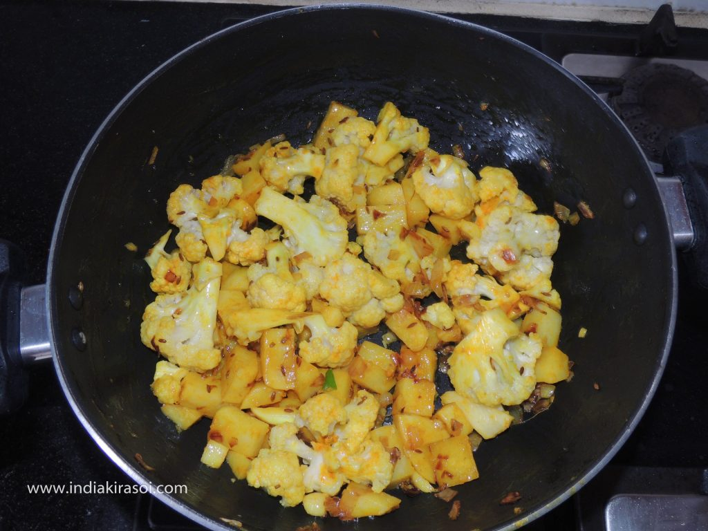 Mix turmeric and salt well with cauliflower and potatoes.