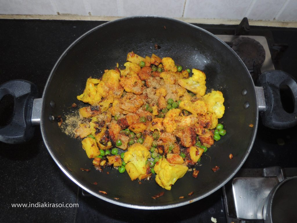 When the potatoes and cauliflower are cooked, add boiled peas to the kadhai/ fry pan.