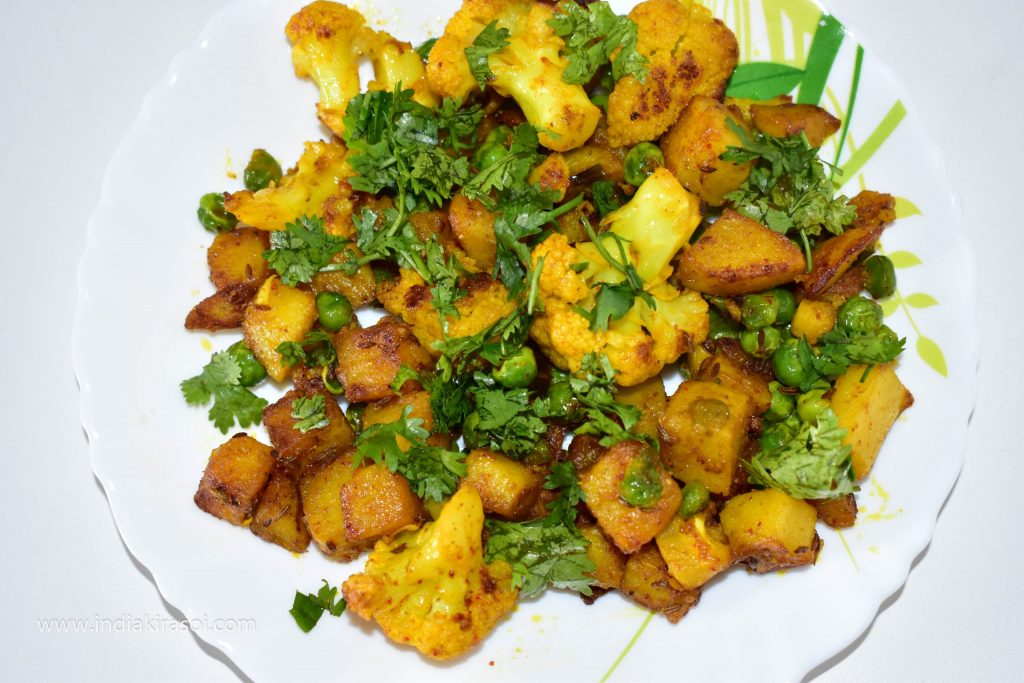 Serve with chopped green coriander on punjabi cauliflower potato dry vegetable.