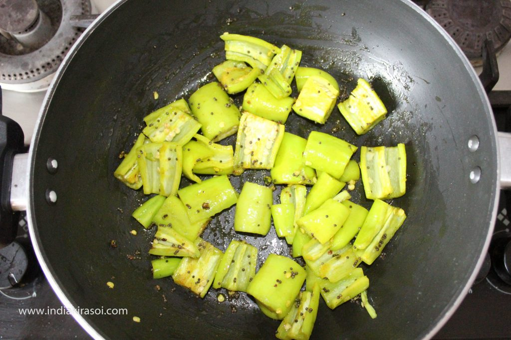 Mix green chilies well with spices.