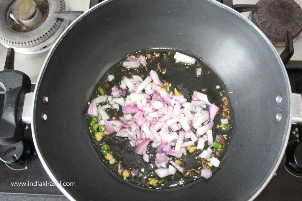 Add chopped onions to the kadhai/ fry pan.