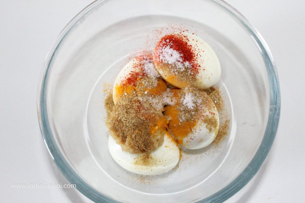Now take eggs in a bowl, along with half a teaspoon coriander powder, half a teaspoon turmeric powder, 1/4 teaspoon red chili powder, half a teaspoon garam masala powder, half a teaspoon salt, 3/4 teaspoon ginger garlic paste over the eggs in the bowl.