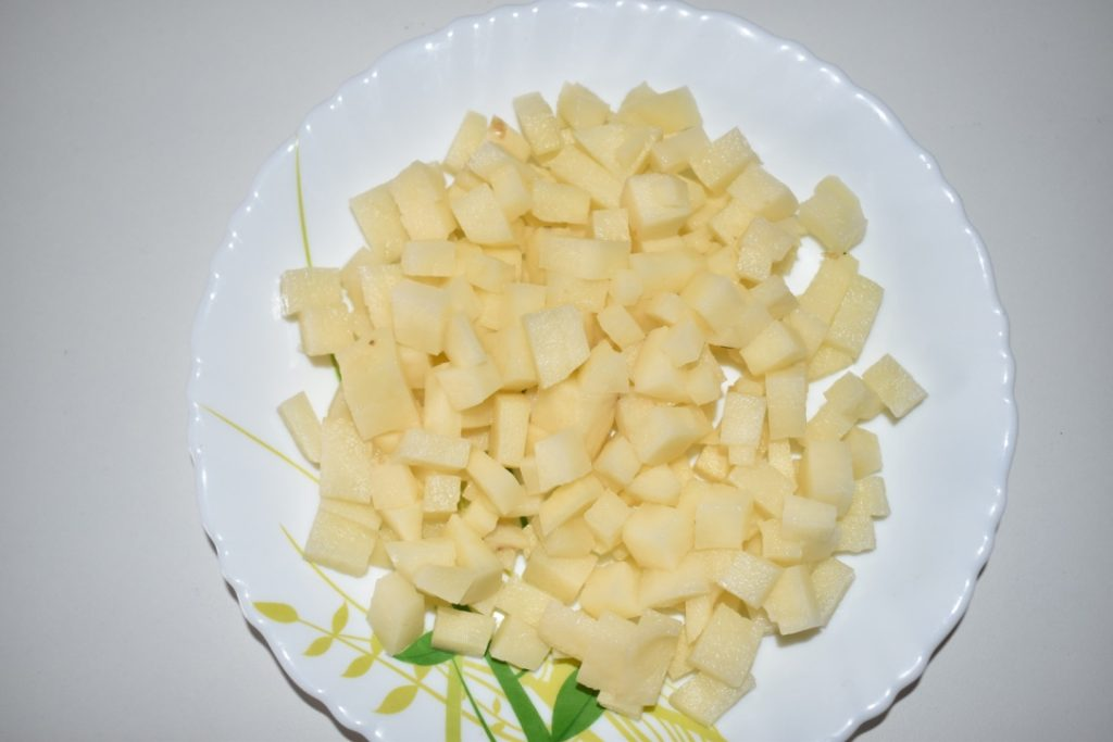 Take 2 medium-sized potatoes, peel the potatoes and cut the potatoes into small square pieces.