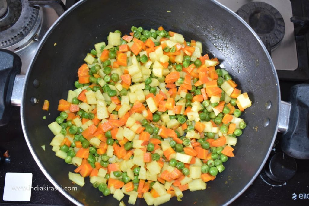 After about 5 minutes, remove the plate of kadhai/ fry pan. Press the potato to see if the potato is cooked.
