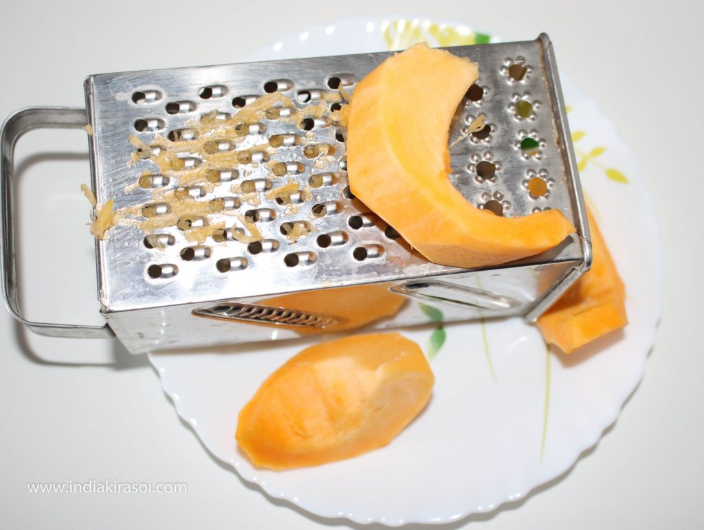 Peel the pumpkin/ kaddu and grate the pumpkin/ kaddu. Be careful to grate the pumpkin/ kaddu.