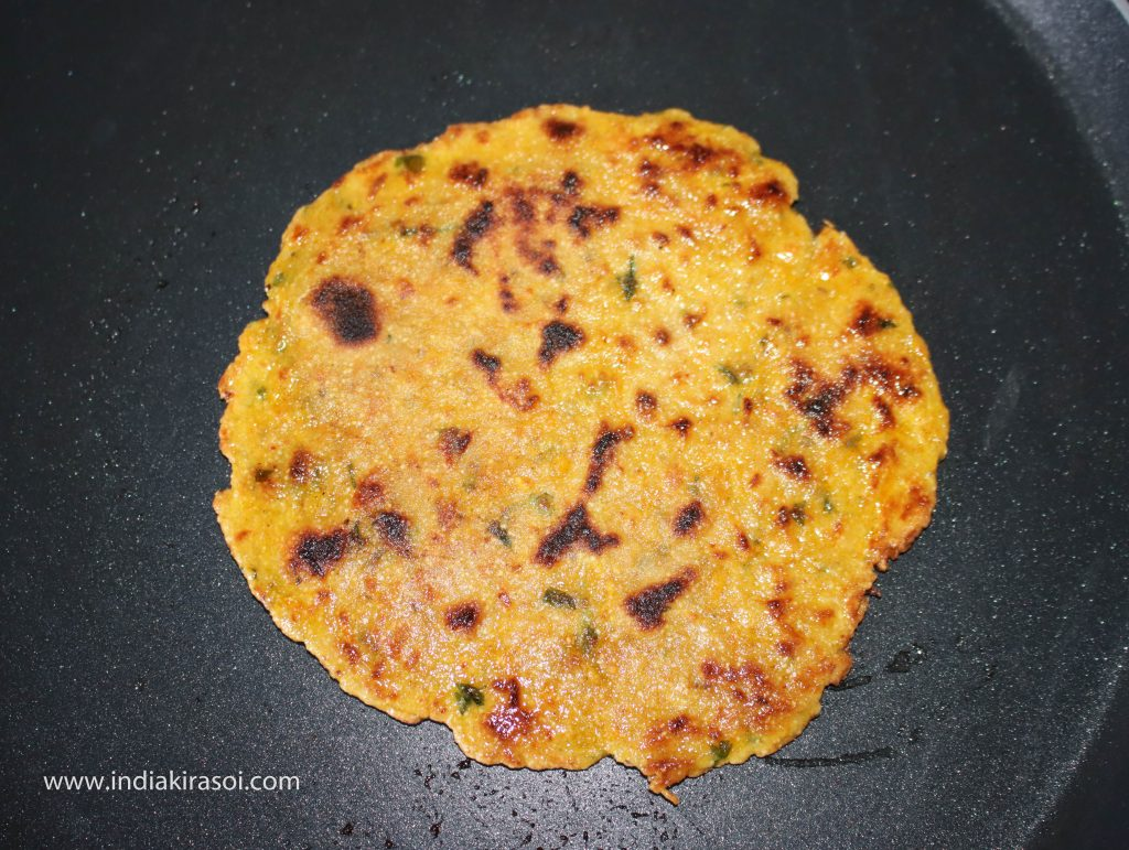 Now change the side of the paratha again, and apply oil or desi ghee or butter on the other side as well.